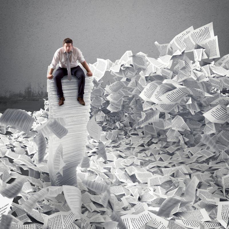 Uomo d'affari con lo strato di carta dovunque Sepolto dal concetto della burocrazia immagine stock libera da diritti