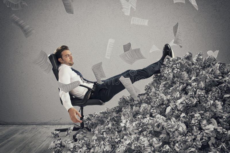 Uomo d'affari con lo strato di carta dovunque Sepolto dalla burocrazia concetto di lavoro eccessivo fotografia stock libera da diritti