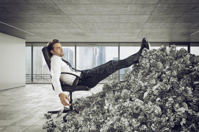 Uomo d'affari con lo strato di carta dovunque Sepolto dalla burocrazia concetto di lavoro eccessivo fotografie stock