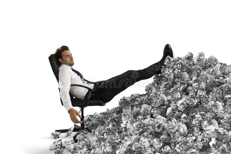 Uomo d'affari con lo strato di carta dovunque Sepolto dalla burocrazia concetto di lavoro eccessivo immagini stock libere da diritti
