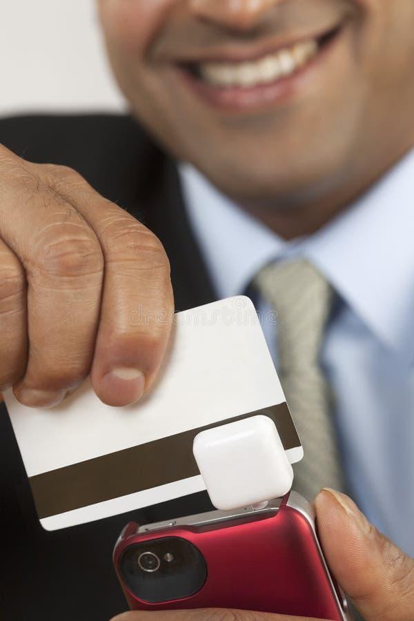 Uomo d'affari con lo swiper della carta di credito immagini stock libere da diritti