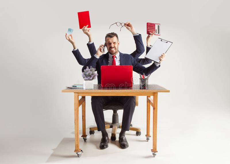 Uomo d'affari con molte mani in vestito elegante che lavora con la carta, documento, contratto, cartella, business plan fotografia stock