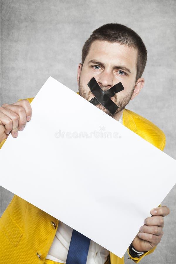 Uomo d'affari con nastro adesivo sulla sua bocca, tenente una carta in bianco fotografie stock libere da diritti