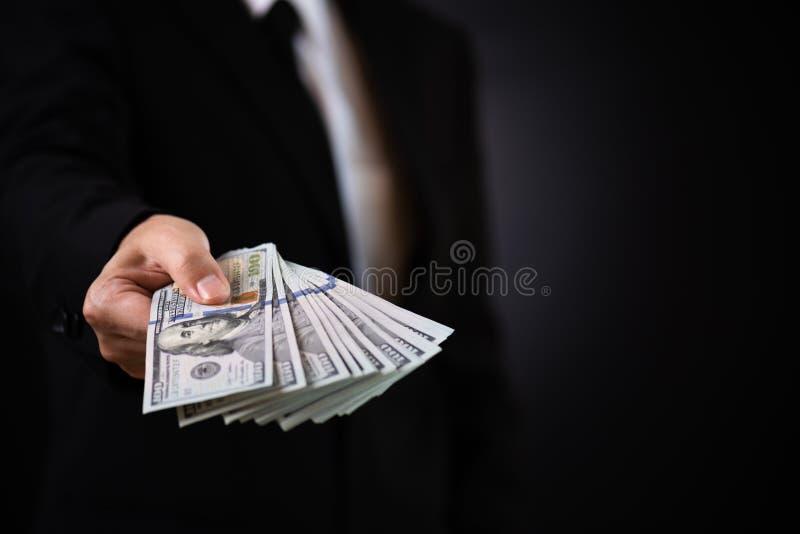 Uomo d'affari con soldi in mano e dando soldi come un dono, le fatture di USD del dollaro americano - investimento, un successo e fotografia stock libera da diritti