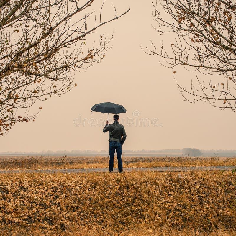 Uomo d'affari con un ombrello all'aperto immagine stock libera da diritti