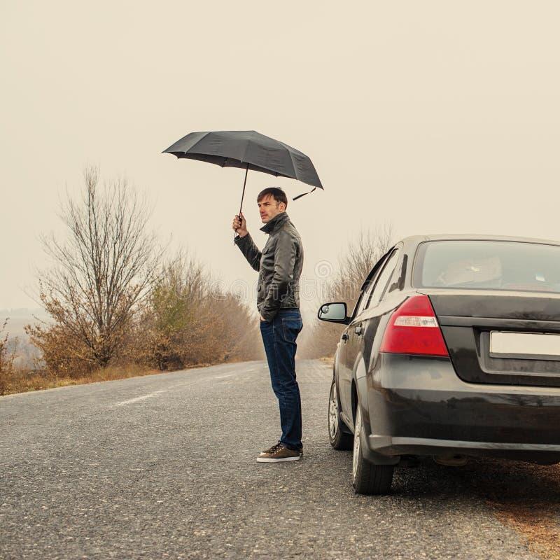 Uomo d'affari con un ombrello nell'automobile fotografia stock