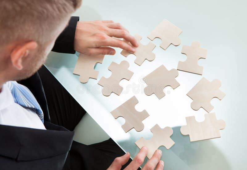 Uomo d'affari con un puzzle immagine stock