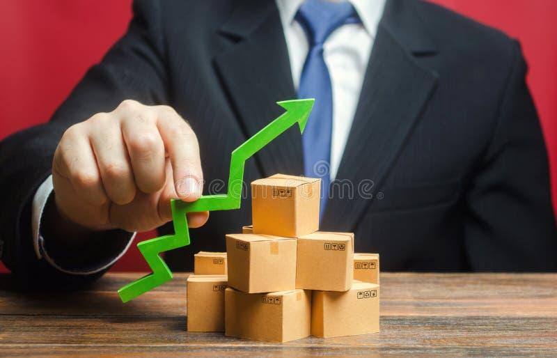 Uomo d'affari con una freccia verde sopra le scatole Aumento del tasso di vendita Aumentare la produzione di beni, aumentare le o fotografia stock