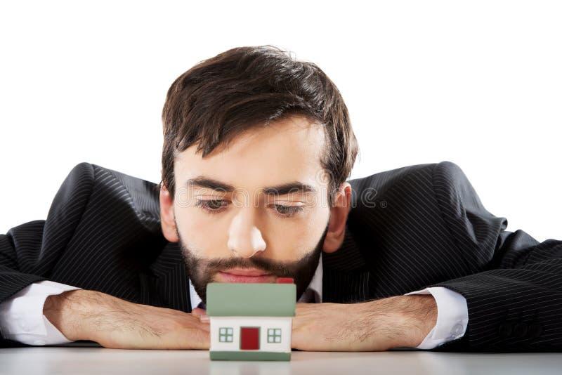 Uomo d'affari con una mini casa nell'ufficio fotografie stock libere da diritti