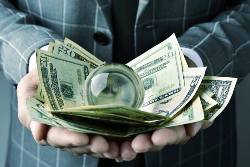 Uomo d'affari con una sfera di cristallo e le banconote in dollari fotografia stock libera da diritti