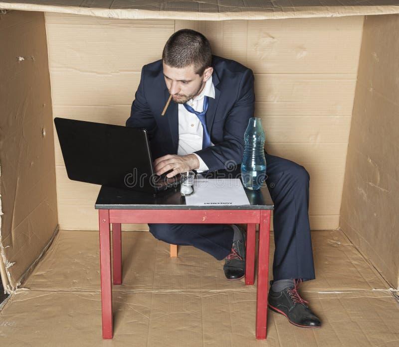 Uomo d'affari con una sigaretta nella sua bocca che lavora ad un computer fotografia stock libera da diritti