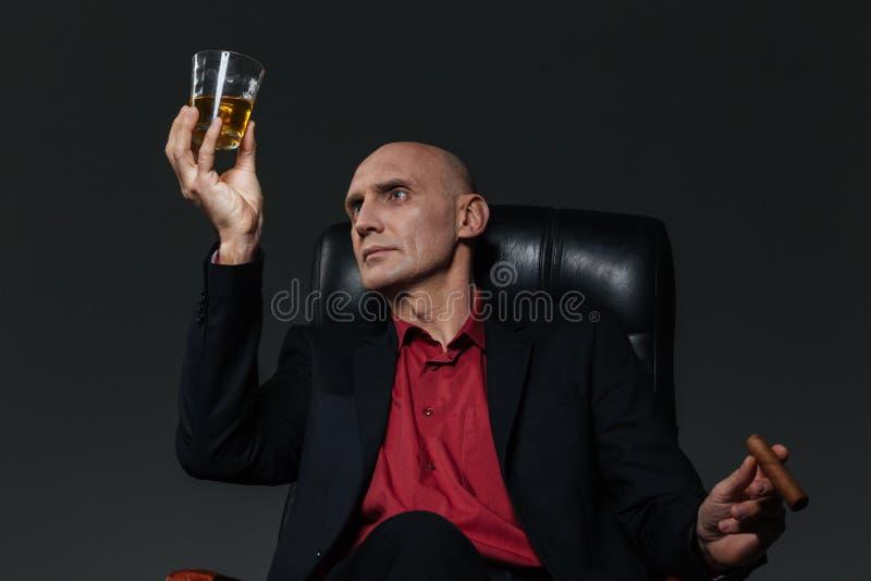 Uomo d'affari con vetro di whiskey e del sigaro che si siedono nella sedia immagini stock