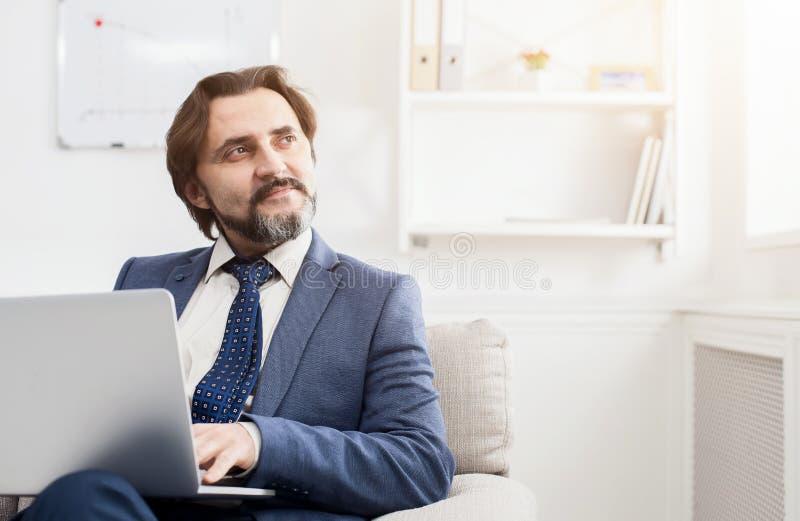 Uomo d'affari concentrato che lavora con il computer portatile immagine stock libera da diritti
