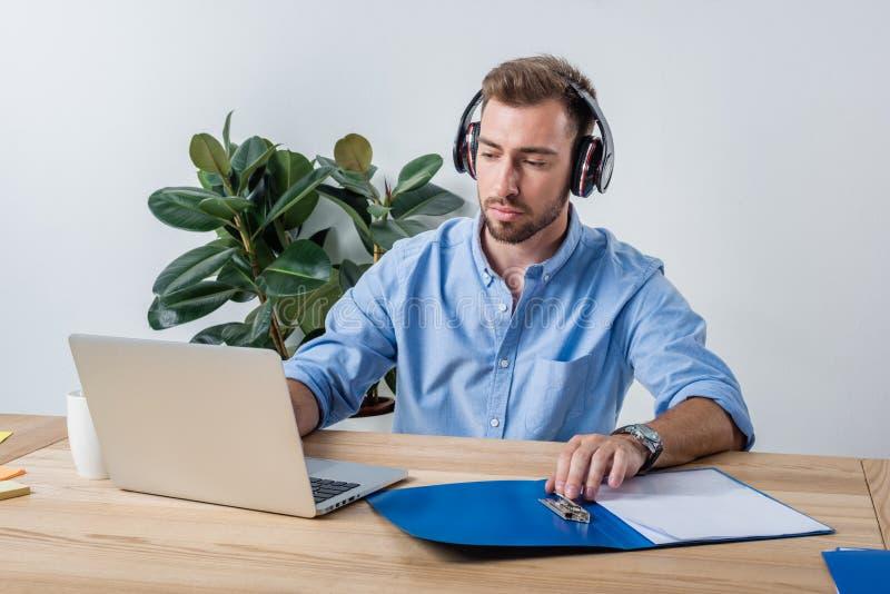 Uomo d'affari concentrato in cuffie che funzionano con i documenti ed il computer portatile in ufficio immagine stock