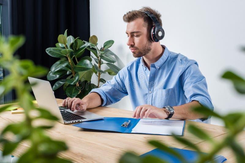 Uomo d'affari concentrato in cuffie che funzionano con i documenti ed il computer portatile in ufficio fotografia stock libera da diritti