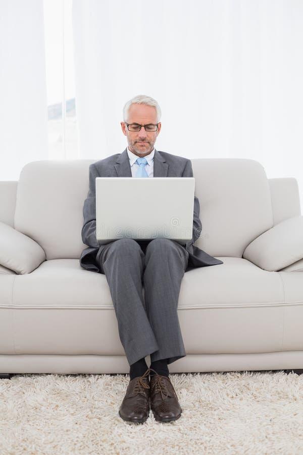 Uomo d'affari concentrato facendo uso del computer portatile a casa fotografia stock