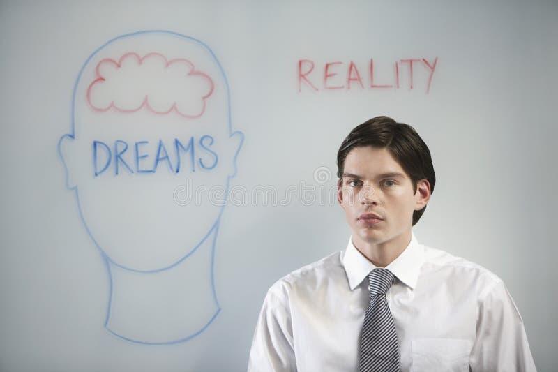 Uomo d'affari Confused Between Dream e realtà fotografia stock