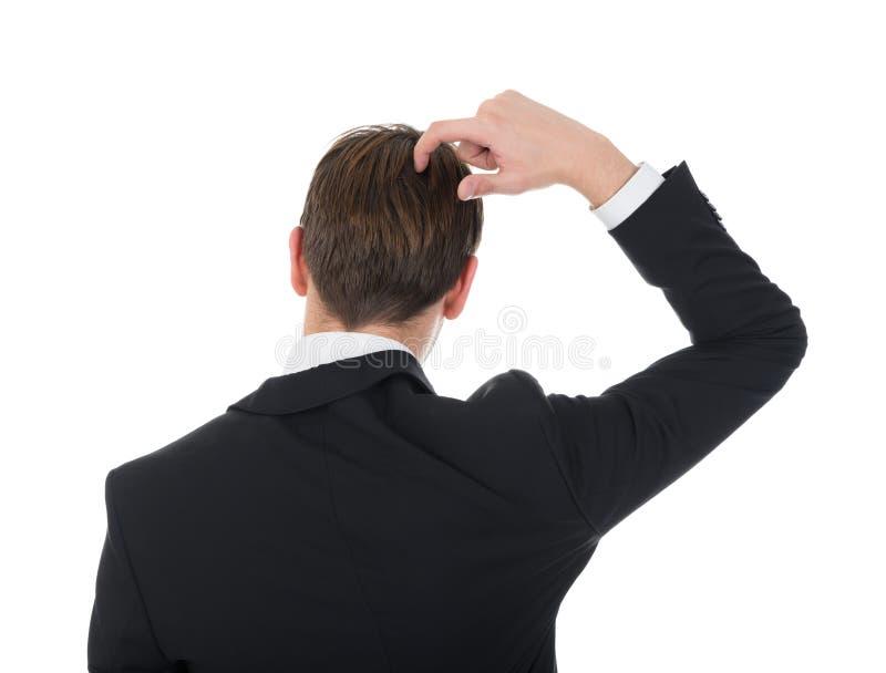 Uomo d'affari confuso che graffia il suo capo fotografia stock libera da diritti