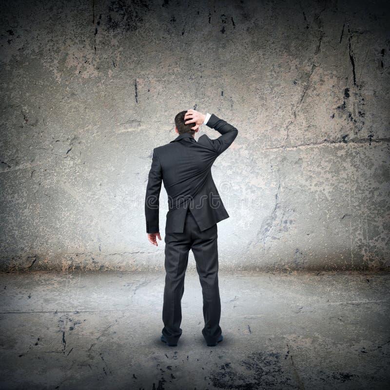 Uomo d'affari confuso davanti alla parete grigia fotografia stock