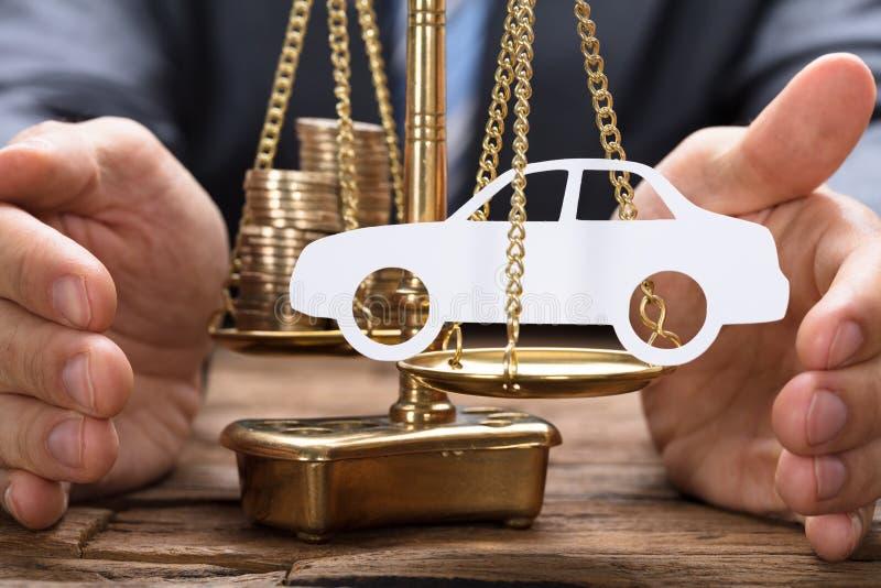 Uomo d'affari Covering Paper Car e monete sulla bilancia immagini stock