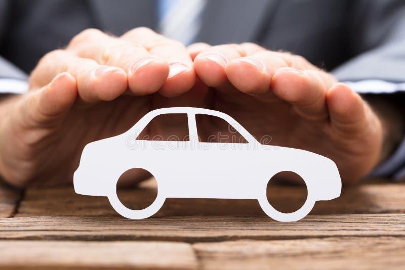 Uomo d'affari Covering Paper Car sulla Tabella immagini stock libere da diritti