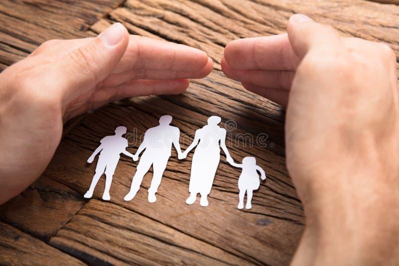 Uomo d'affari Covering Paper Family alla Tabella di legno immagini stock