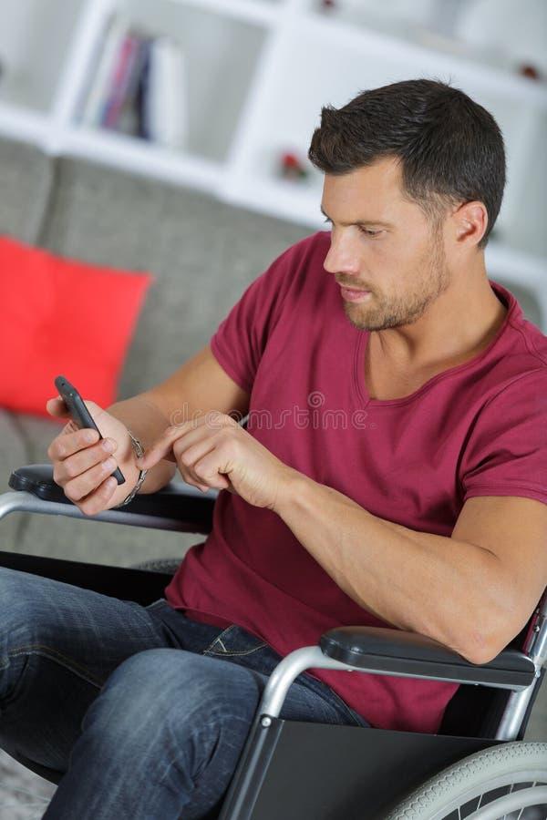 Uomo d'affari creativo in telefono della tenuta della sedia a rotelle all'ufficio fotografia stock