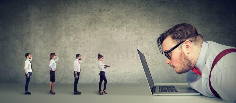Uomo d'affari curioso che esamina computer portatile che analizza gruppo di persone di affari che si applicano online per un lavo immagini stock libere da diritti