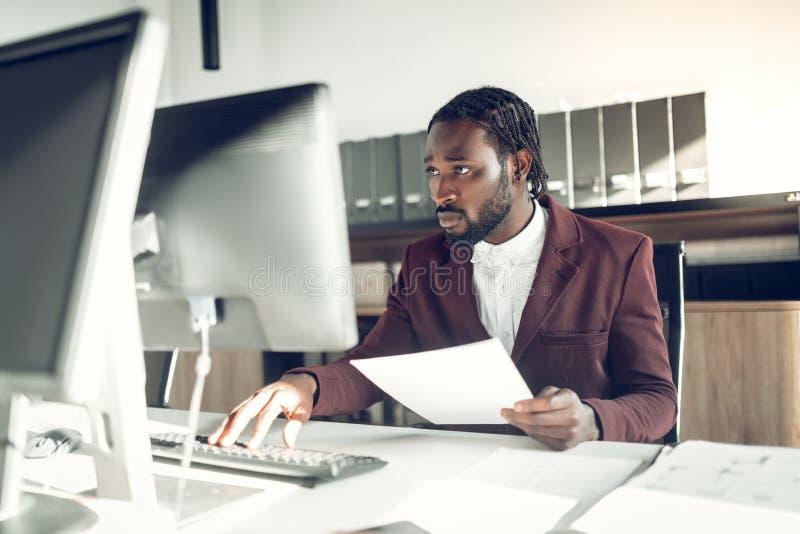 Uomo d'affari dalla carnagione scura che lavora al computer nell'ufficio fotografia stock libera da diritti