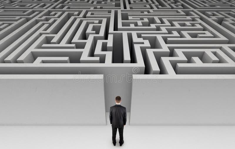 Uomo d'affari davanti ad un labirinto enorme fotografia stock libera da diritti