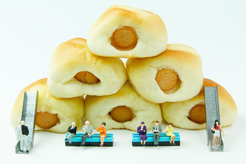 Uomo d'affari dei giocattoli e pane minuscoli della salsiccia Fondo dell'alimento di concetto fotografie stock