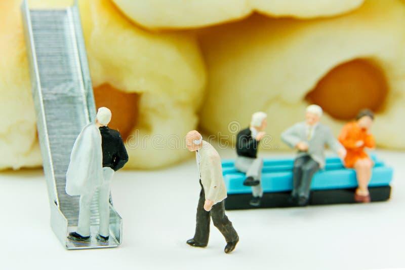 Uomo d'affari dei giocattoli e pane minuscoli della salsiccia Fondo dell'alimento di concetto immagine stock
