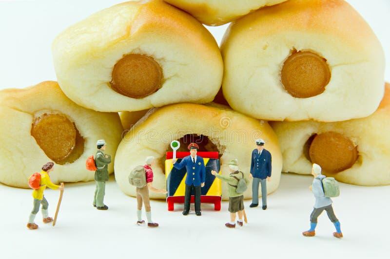 Uomo d'affari dei giocattoli e pane minuscoli della salsiccia Fondo dell'alimento di concetto immagine stock libera da diritti