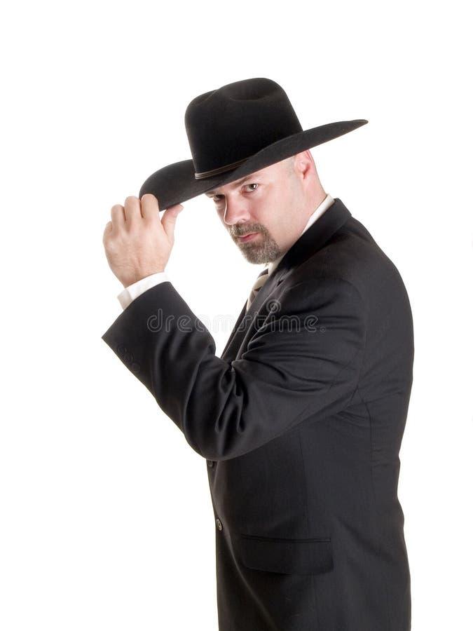 Uomo d'affari del cowboy che capovolge cappello immagini stock libere da diritti
