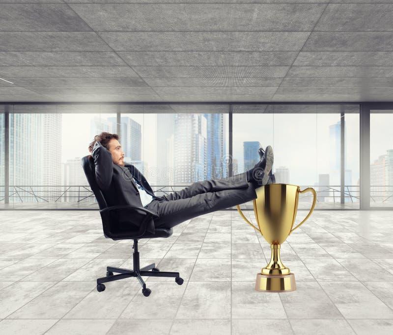 Uomo d'affari del vincitore che si rilassa sopra una tazza dorata fotografia stock libera da diritti