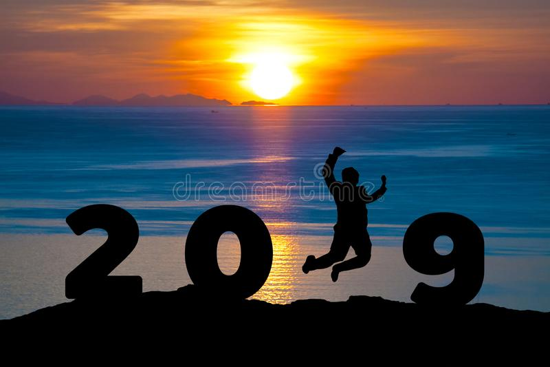 Uomo d'affari 2019 della siluetta di concetto di Newyear il giovane sta saltando a 2019 nuovi anni fotografie stock libere da diritti