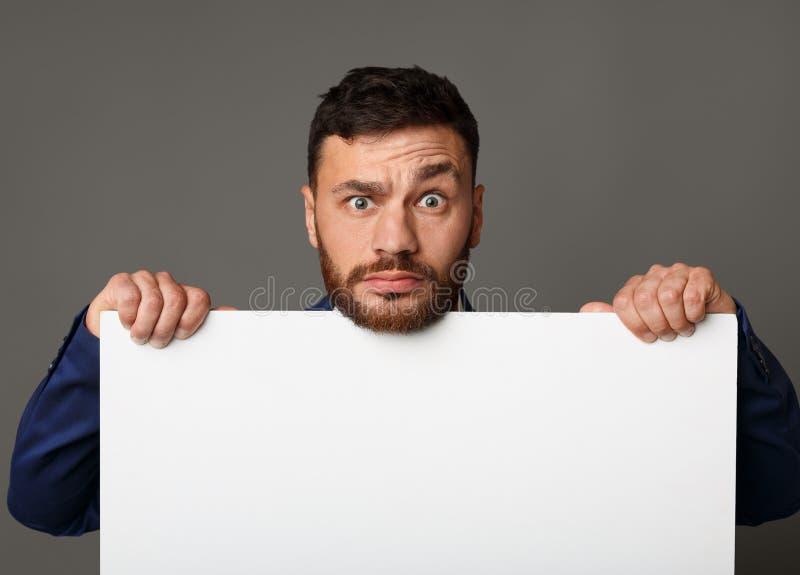 Uomo d'affari deludente che mostra a spazio in bianco carta vuota bianca fotografia stock libera da diritti
