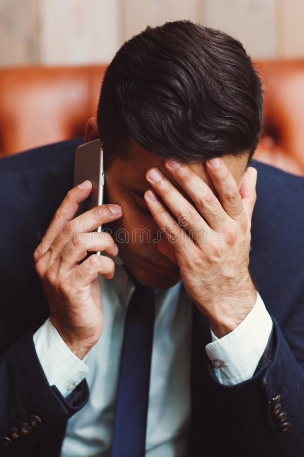 Uomo d'affari depresso che parla sul telefono fotografia stock libera da diritti