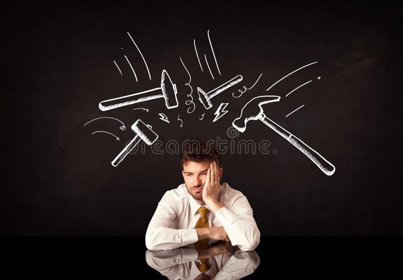 Uomo d'affari depresso che si siede nell'ambito dei segni del martello immagine stock
