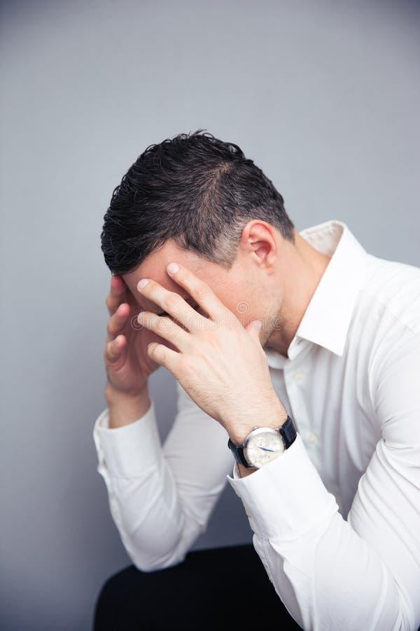 Uomo d'affari depresso sopra fondo grigio immagini stock