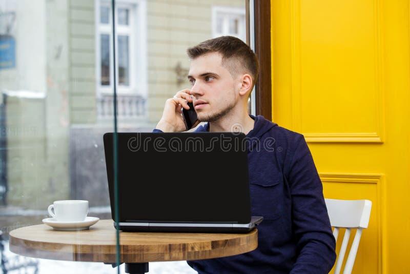 Uomo d'affari di collegamento di Internet di wifi del computer portatile di uso della mano dell'uomo occupato al computer di batt fotografia stock