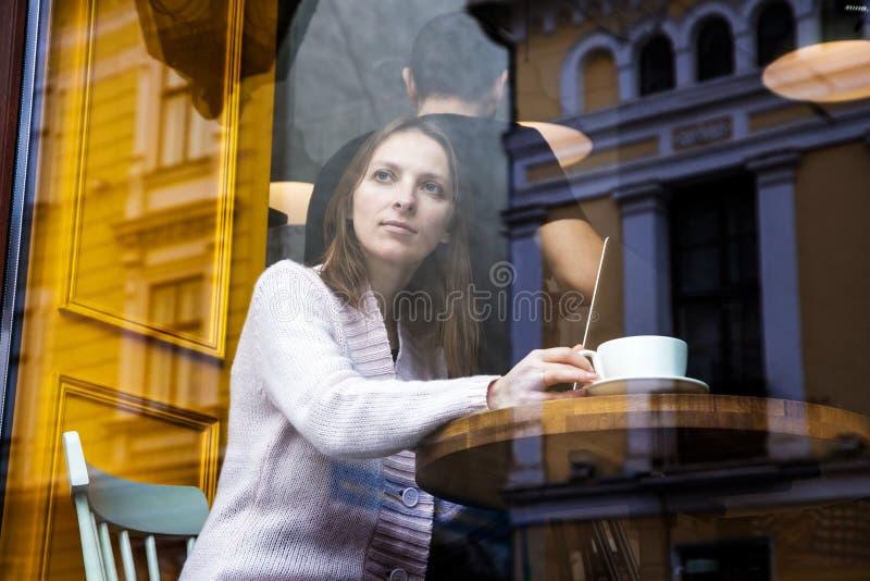 Uomo d'affari di collegamento di Internet di wifi del computer portatile di uso della mano della donna occupato alla seduta di ba immagini stock libere da diritti