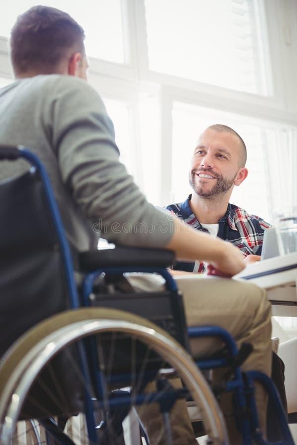 Uomo d'affari di handicap con il collega in ufficio creativo fotografia stock libera da diritti