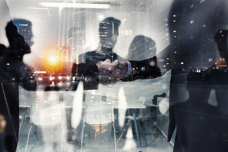 Uomo d'affari di handshake in ufficio Concetto di lavoro di squadra e dell'associazione Doppia esposizione immagini stock