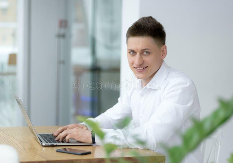 Uomo d'affari di mezza età alla moda che esamina macchina fotografica con il sorriso a trentadue denti mentre lavorando al proget immagini stock libere da diritti