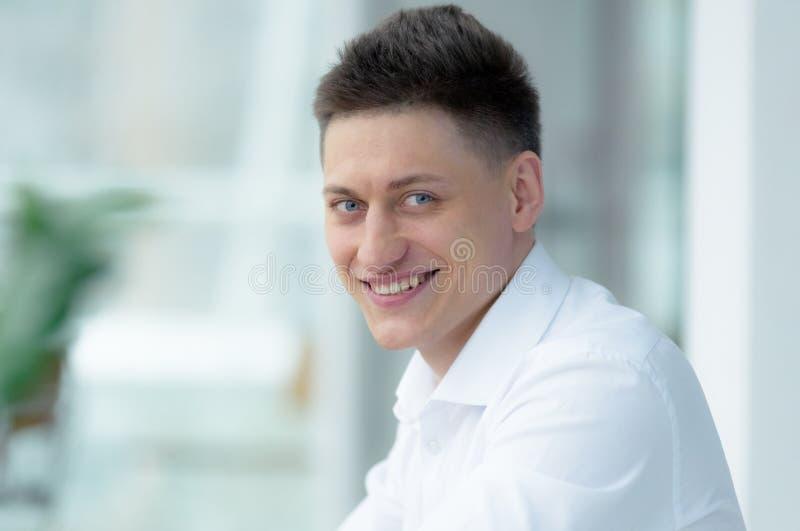 Uomo d'affari di mezza età alla moda che esamina macchina fotografica con il sorriso a trentadue denti mentre lavorando al proget fotografia stock libera da diritti