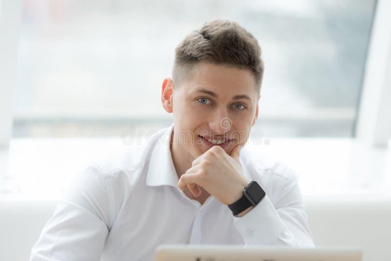 Uomo d'affari di mezza età alla moda che esamina macchina fotografica con il sorriso a trentadue denti mentre lavorando al proget immagine stock