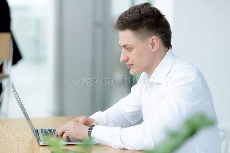 Uomo d'affari di mezza età alla moda con il sorriso mentre lavorando al progetto immagini stock libere da diritti