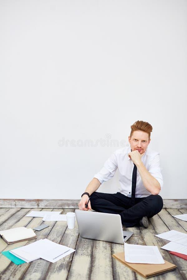 Uomo d'affari di pensiero Sitting sul pavimento dell'ufficio immagini stock libere da diritti