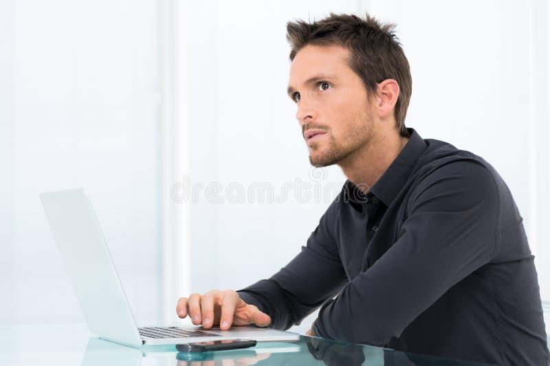 Uomo d'affari di pensiero Working On Laptop fotografia stock libera da diritti